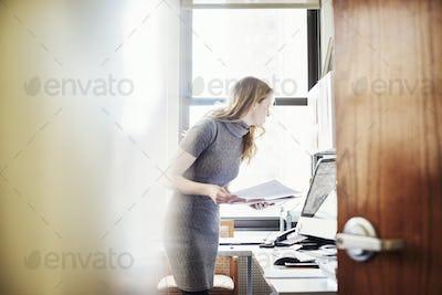 A woman in an office, seen through an open door.