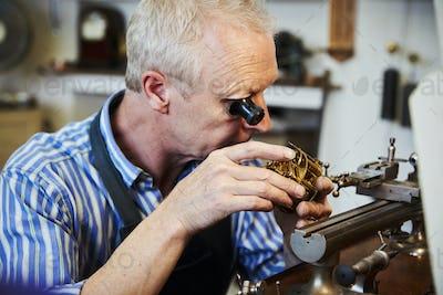 A clock maker using an eyeglass to work on small mechanisms in a clock.