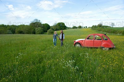 Man and woman walking hand in hand across a meadow, vintage red car parked close by.