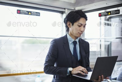 Businessman wearing suit standing on a commuter train, holding laptop.