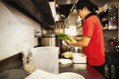 The ramen noodle shop. A chef working in a kitchen preparing food using a stove and large pans.