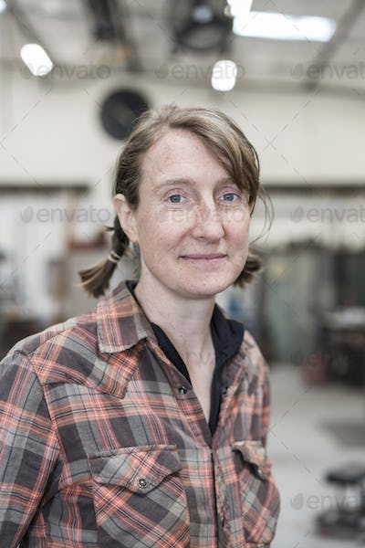 Blond woman wearing checkered shirt standing in metal workshop, smiling at camera.