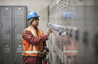 Black man factory worker wearing safety vest and getting into his locker in a factory break room.