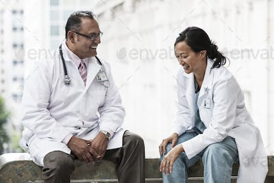 HIspanic man and asian woman doctors conferring over a case in a hospital.