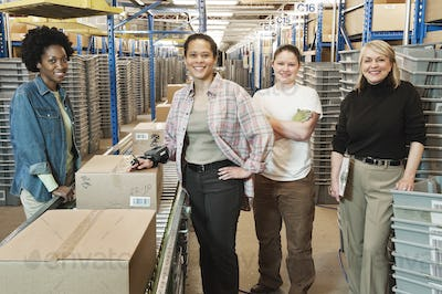 Team portrait of multi-ethnic female warehouse workers working next to a motorzied feed conveyor in