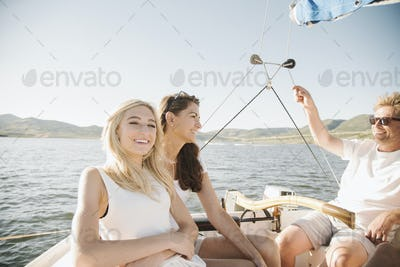Man, woman and their blond teenage daughter on a sail boat.