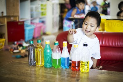 Young boy playing with a selection of bottles with colourful liquids in a Japanese preschool.
