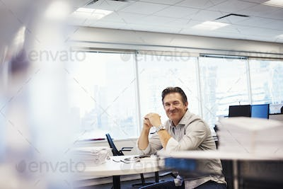 A man sitting at a table in an office, looking into shot and smiling.