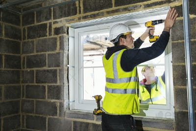 A workman on a construction site, a builder in hard hat using an electric drill on a window sill.