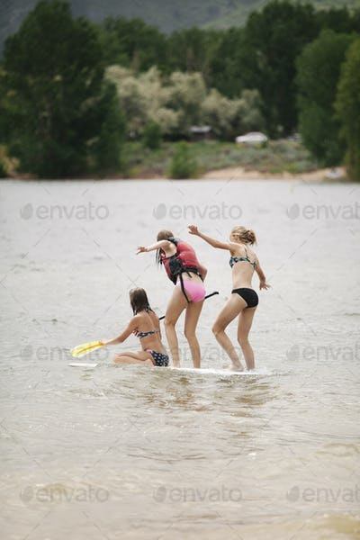 Three teenage girls on a paddle board on a lake.