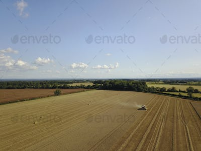 A drone shot of fields in a farming landscape, and a combine harvester working harvesting a crop.
