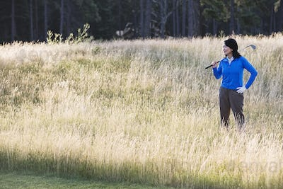 A young senior woman surveys her next shot from the heavy rough.