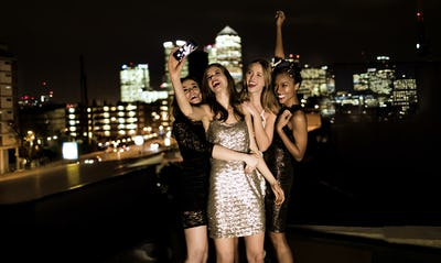 Group of young women standing on a rooftop posing for a photograph.