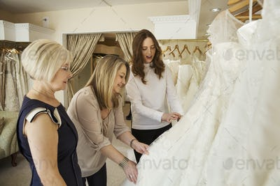 Three women, a client and two retail advisors in a wedding dress shop, looking through the choice of