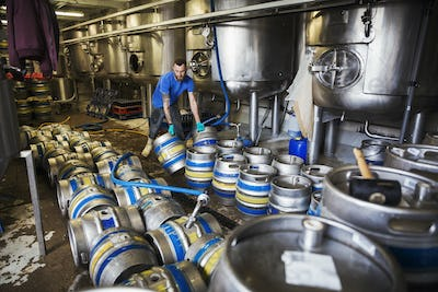 Man working in a brewery, carrying metal beer kegs.