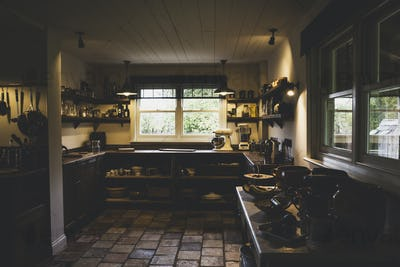 Interior view of kitchen with stone tile floor, wooden ceiling and two sash windows, antique wooden