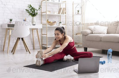 Yoga instructor running online training session via laptop at home