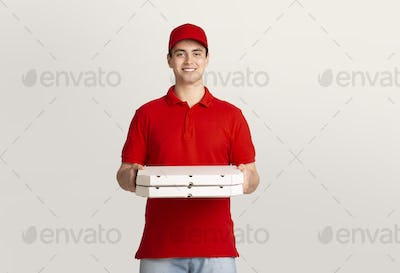 Food delivery. Smiling courier holds boxes with pizza