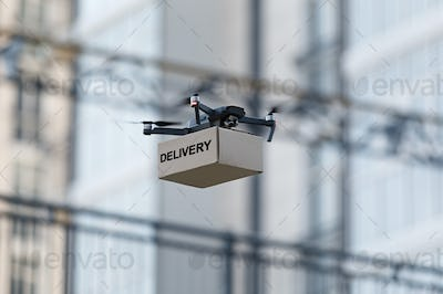 Drone with cardboard parcel and remote control delivering package