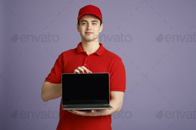 Order courier at home online. Deliveryman holding laptop with blank screen