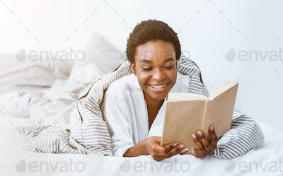 Morning book reading. African american woman wrapped in blanket