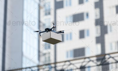 Modern quadrocopter robots delivery methods, blurred city