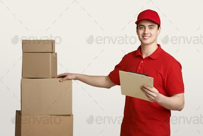Caring for parcel. Smiling deliveryman in red uniform checks boxes in warehouse with tablet