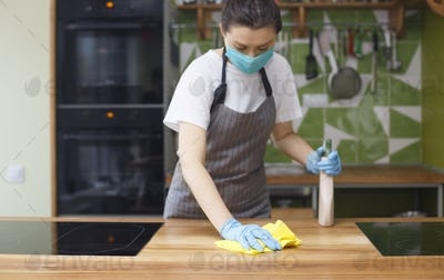 Woman cleaning kitchen with disinfecting spray and microfiber