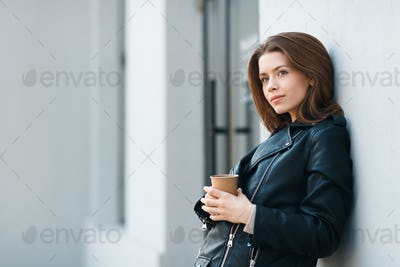 Happy casual brunette female staying near grey wall with coffee