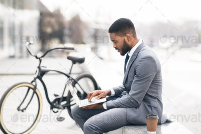 Handsome guy working on laptop sitting on parapet