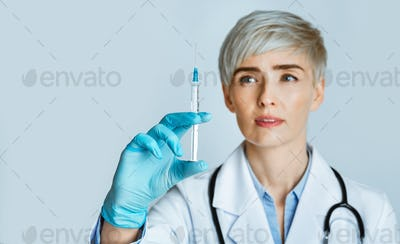 Nurse makes injection. Woman in white coat with medical gloves looks at syringe