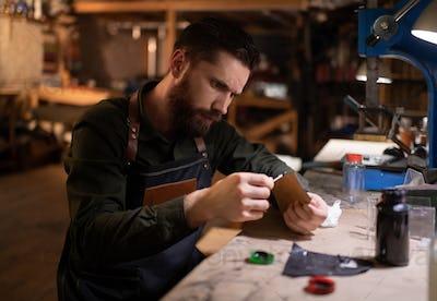 Craftsman applying glue on leather