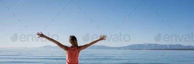 Young woman standing by the morning sea greeting the new day