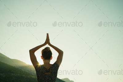 Young woman doing yoga workout at sunrise