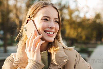 Portrait of joyful blonde woman smiling and talking on cellphone