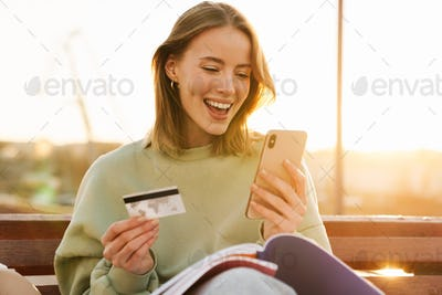 Portrait of excited young woman holding cellphone and credit card