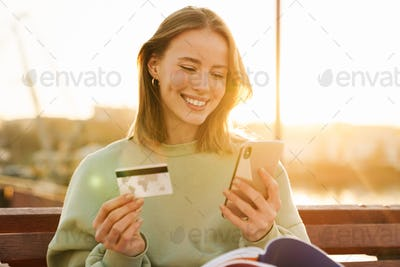 Portrait of smiling young woman holding cellphone and credit card
