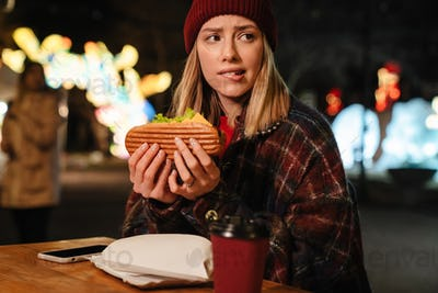 Photo of scared nice woman eating sandwich while sitting in street cafe