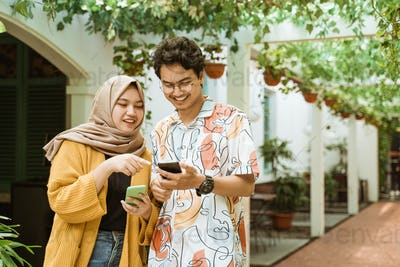asian young couple laughed while holding a cellphone