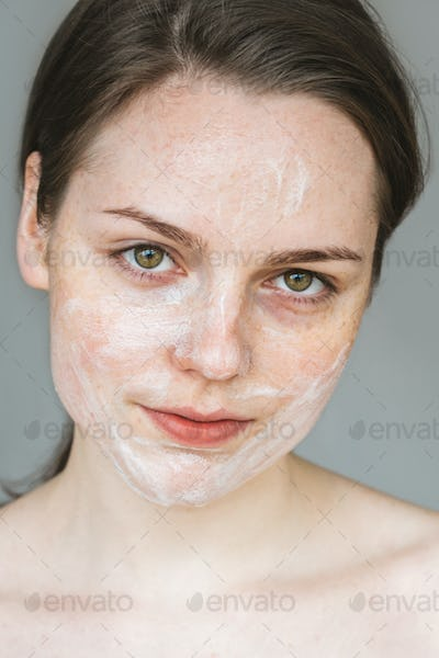 Young beautiful woman washing face with hands by soap. Studio shot