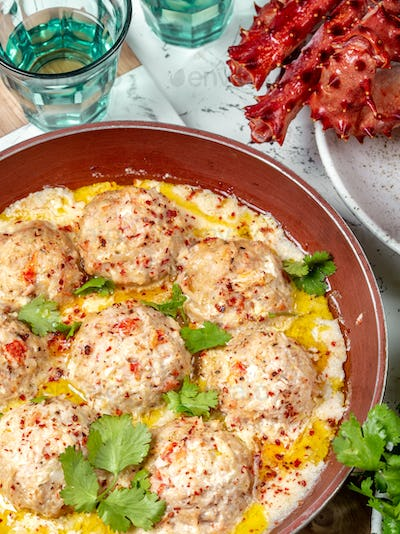 meatballs in white creamy sauce in red pan
