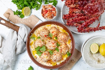 crab meatballs in white creamy sauce in red pan, whole king crab,