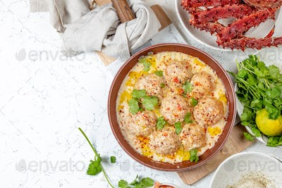 crab meatballs in white creamy sauce in red pan, whole king crab, cilantro, lemon