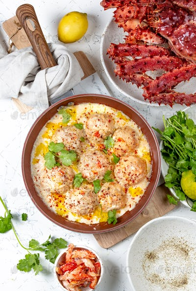 CRABMEATBALLS crab meatballs in white creamy sauce in red pan, whole king crab, cilantro, lemon and