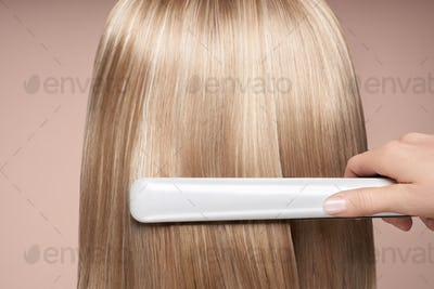 Hairdresser straightening long hair with hair irons