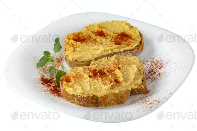 Two open sandwiches with hummus and paprika powder