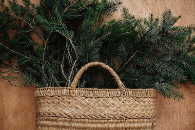 Rustic basket with fir branches on rustic wooden background. Flat lay