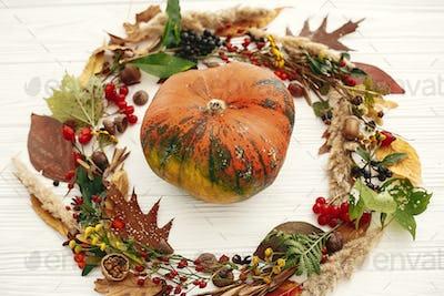 Pumpkin in autumn wreath of fall leaves