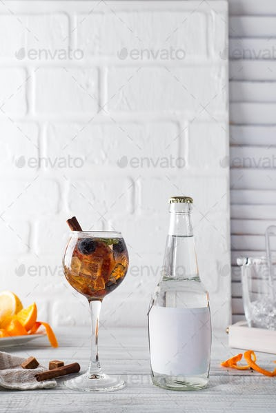 Cocktail with iced tea, whiskey, berries and ice in a glass with a bottle of tonic and a place under