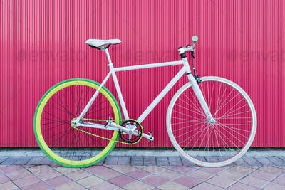 City bicycle fixed gear on red wall.
